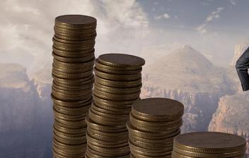 Hombre sobre una columna de monedas frente a otras columnas con más monedas
