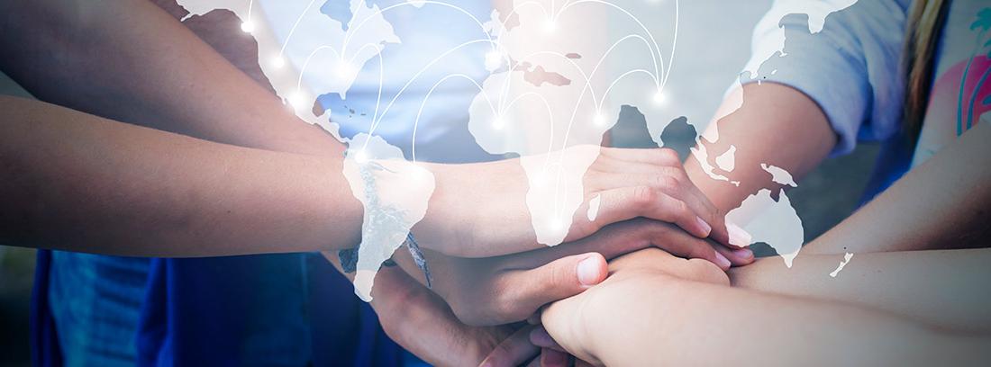 Varias personas juntando las manos con un mapa mundial sobre ellas