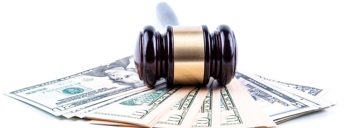 Mazo de juez sobre un fajo de billetes