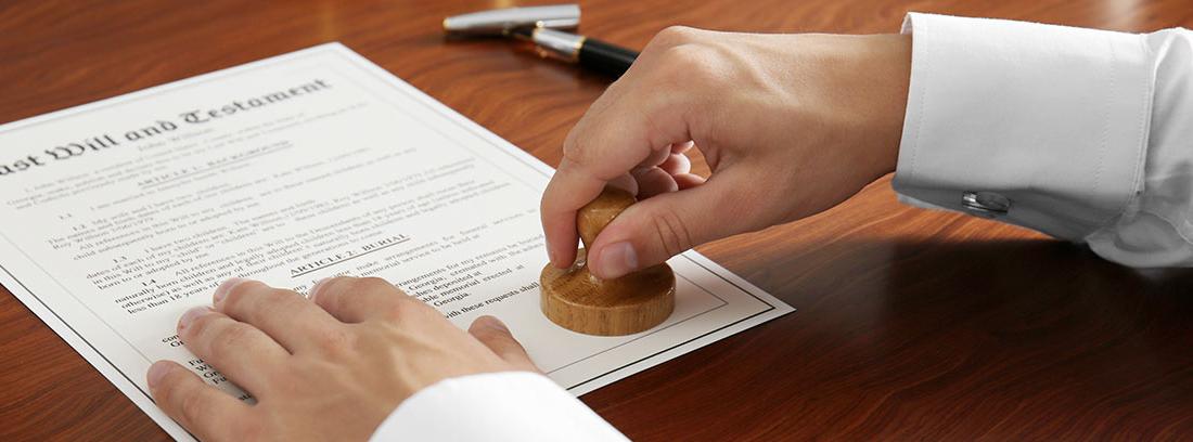 """Manos de hombre estampando un sello sobre unos papeles en los que puede leerse """"Last Will and Testament"""""""