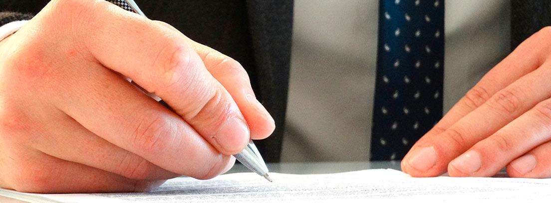 Mano con un boli escribiendo en un papel