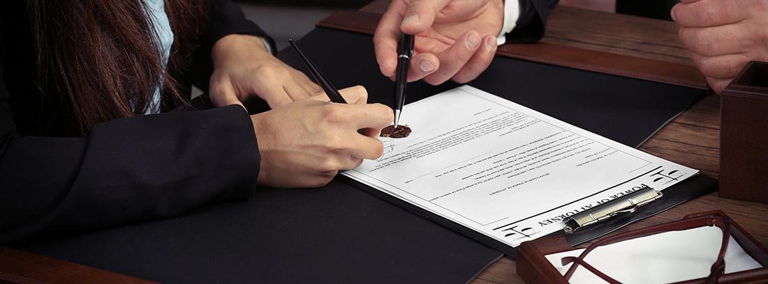 Manos firmando un poder notarial