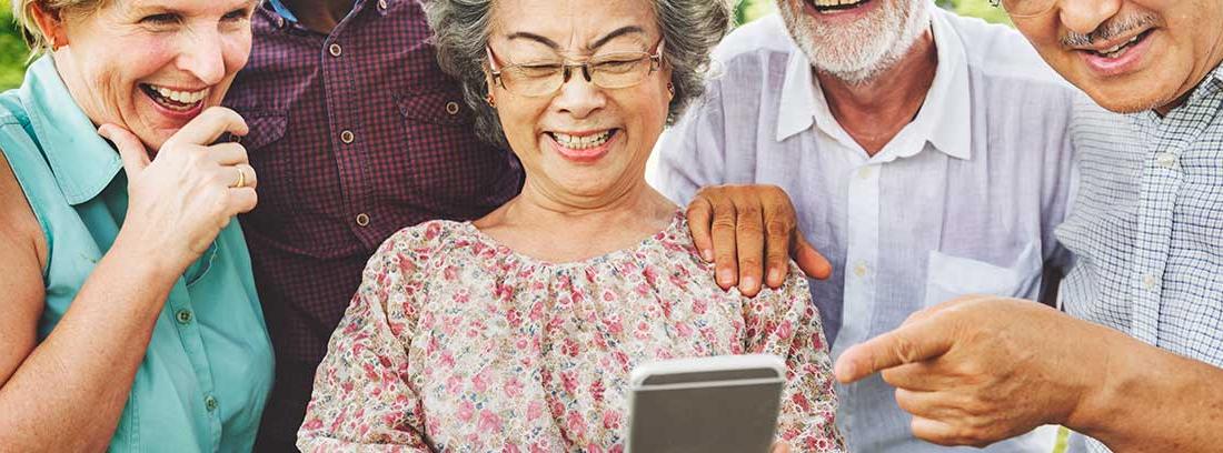 Grupo de personas mayores sonrientes mirando un teléfono móvil