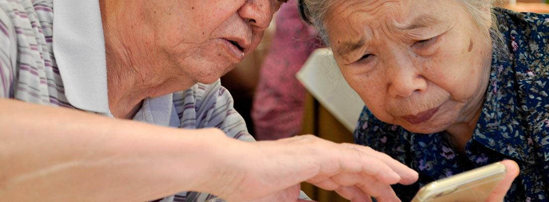 Dos ancianos mirando un teléfono móvil
