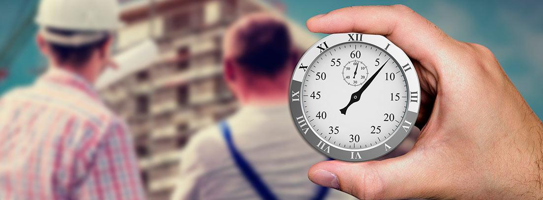 Dos trabajadores de espaldas y una mano sosteniendo un cronómetro