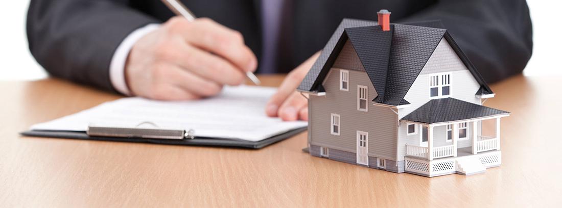 Hombre firmando unos papeles del Registro de la Propiedad junto a la maqueta de una casa