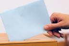 Mano de mujer metiendo un sobre con su voto en una urna