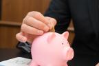 Hombre con traje metiendo monedas en una hucha de cerdo sobre unos papeles con gráficos