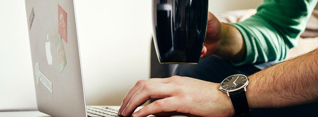 Hombre con una mano sujetando una taza y otra mano sobre un ordenador