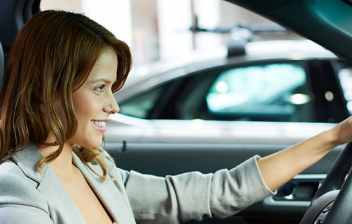 Mujer sonriente conduciendo un coche