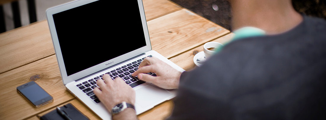 Hombre de espaldas teclea sobre ordenador portátil junto a libreta con bolígrafo