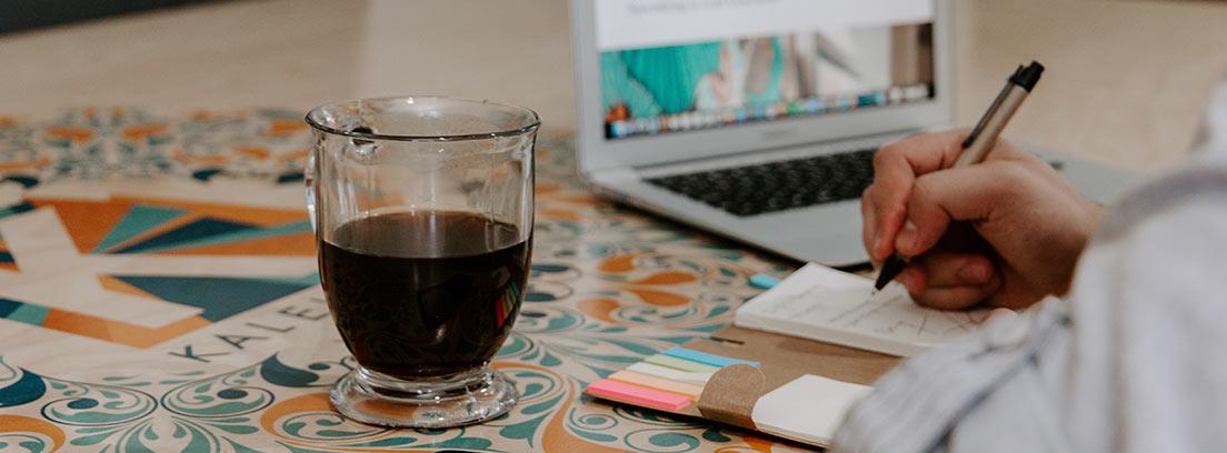 Persona escribiendo con bolis sobre libreta junto a teléfono móvil y vaso de cristal con café