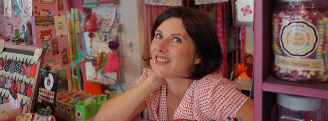 Mujer apoyada sobre un mostrador de negocio
