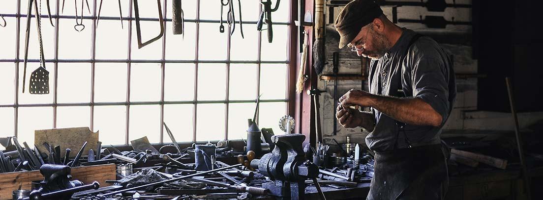 Hombre en taller de soldadura con herramientas y piezas a su alrededor