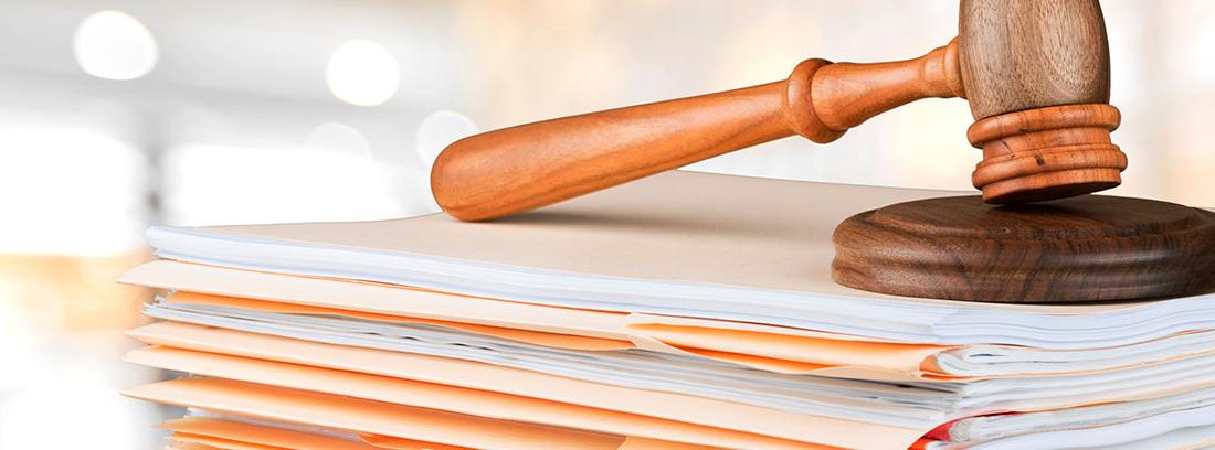 Mazo de juez sobre carpetas de papel con documentación
