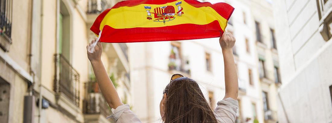 Mujer de espaldas levantando una bandera española con las dos manos