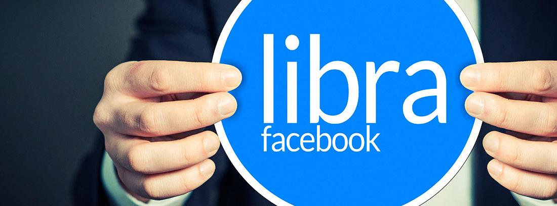 """Manos sujetando un cartel en el que se lee """"libra Facebook"""""""