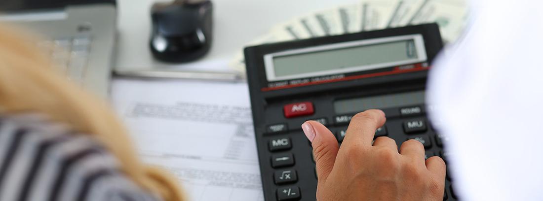 Mujer usando una calculadora para analizar los gastos de la cuesta de septiembre