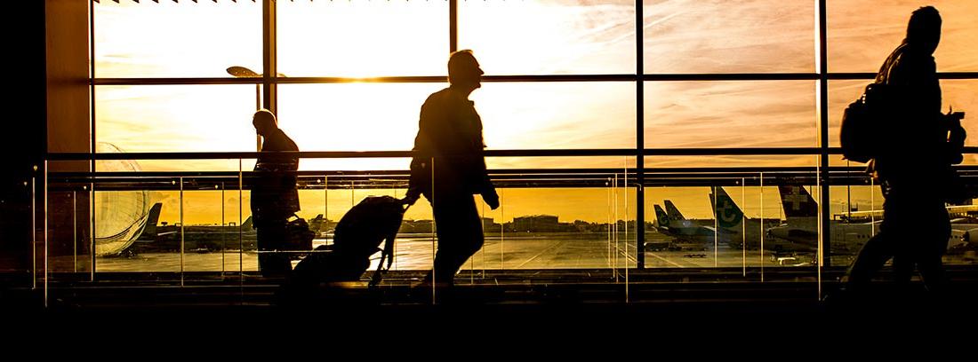 Silueta de varias personas con maletas en un aeropuerto