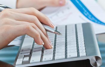 Manos de mujer sobre un teclado de ordenador, con un boli y papeles
