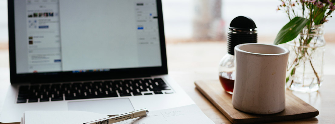 Mesa con agenda abierta delante de ordenador portátil y junto a vaso blanco