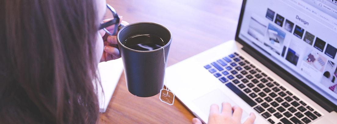 Persona con taza de infusión en la mano y la otra en teclado de ordenador portátil
