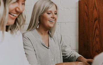 Dos mujeres delante de ordenadores portátiles y tecleando con gesto sonriente