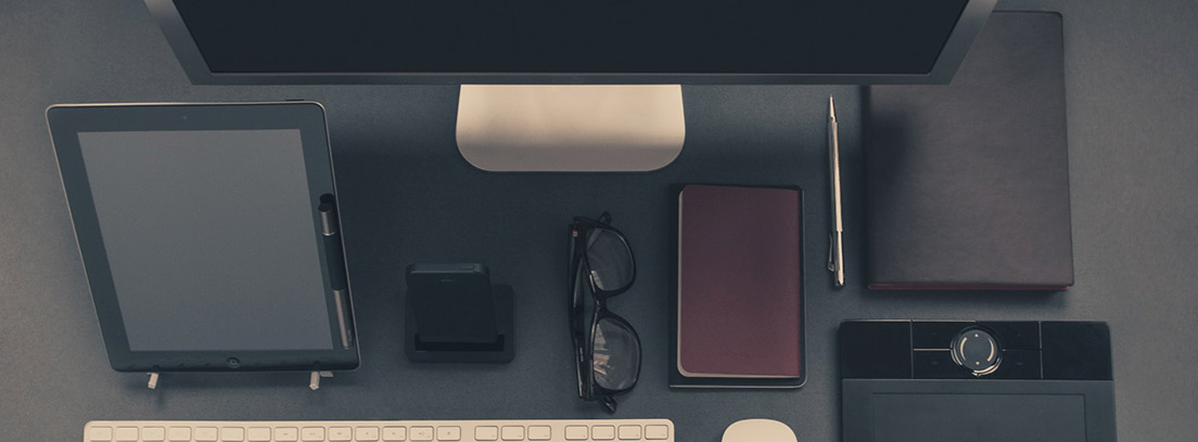 Gadgets tecnológicos rodeando unas gafas y una libreta