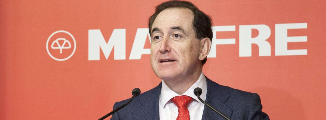 Antonio Huertas, presidente de MAPFRE ante un fondo rojo con las letras de MAPFRE en blanco.