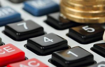 Monedas y lápiz sobre una calculadora