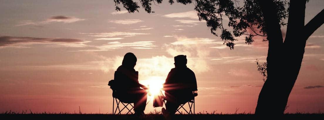 Una pareja ve el atardecer sentada en sillas