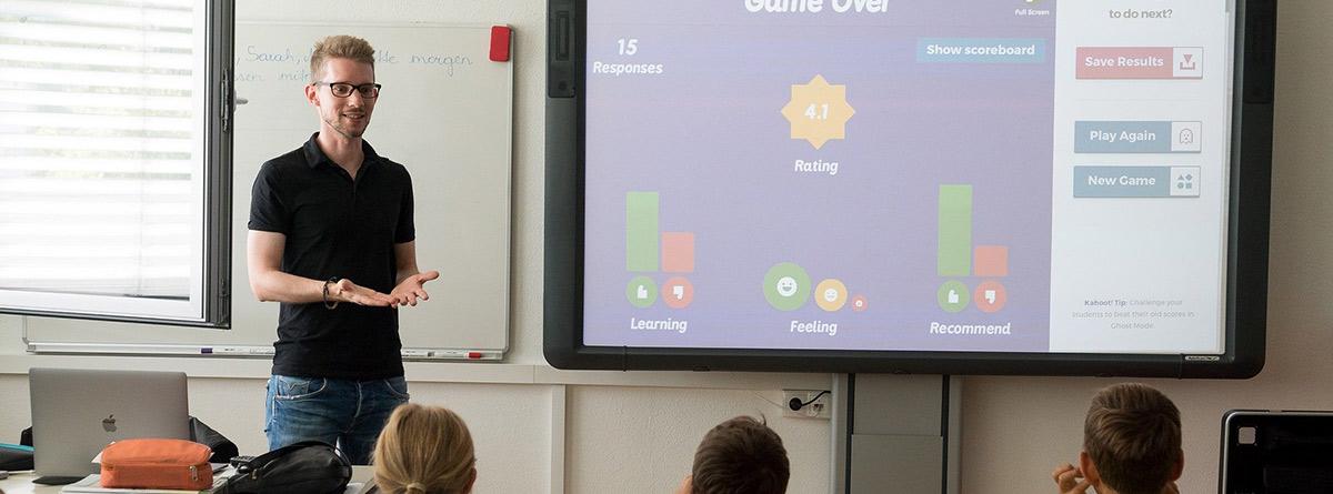 Profesor junto a una pizarra digital dando una clase