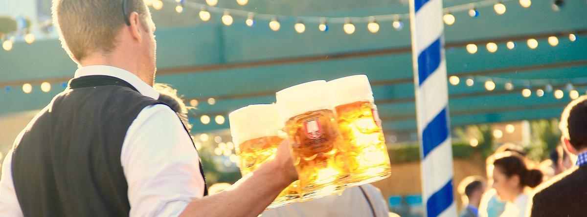 Camarero llevando tres jarras de cerveza