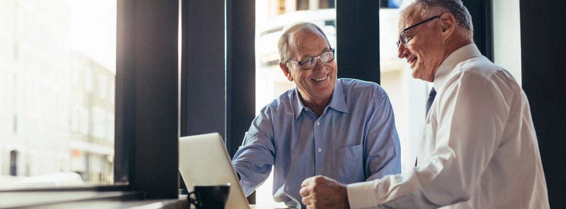 Persona mayor en el trabajo utilizando un ordenador portátil y hablando con otro hombre