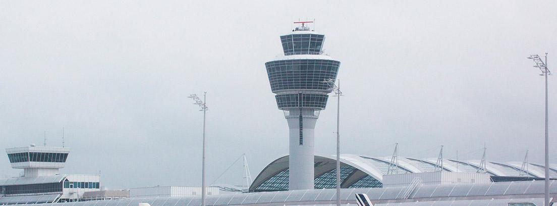 Varios aviones parados en el aeropuerto con torre de control al fondo