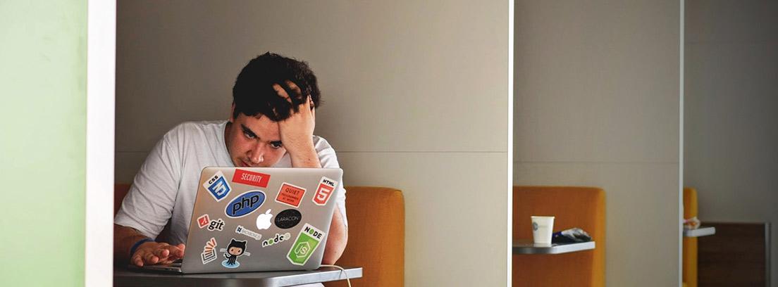 Hombre joven sentado frente a un ordenador