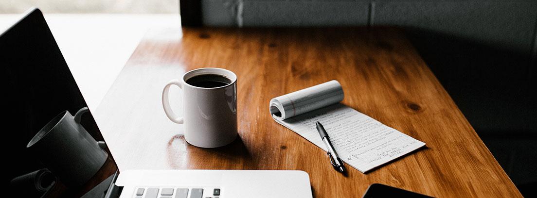 Ordenador portátil junto a móvil, bloc de notas, taza y boli.