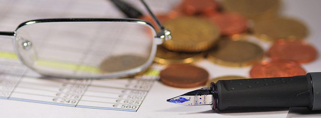 gafas, monedas y boli sobre papeles con anotaciones de cantidades de dinero en euros