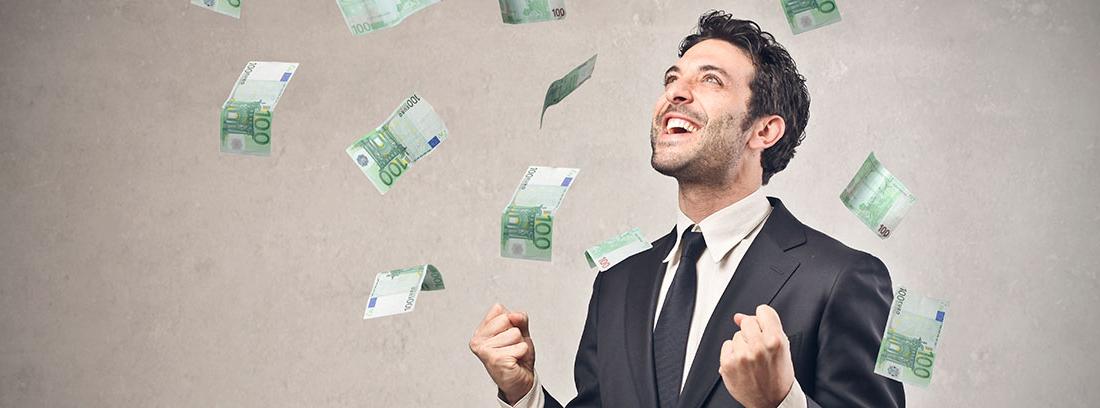 Hombre con traje y gesto sonriente bajo una lluvia de billetes de euro