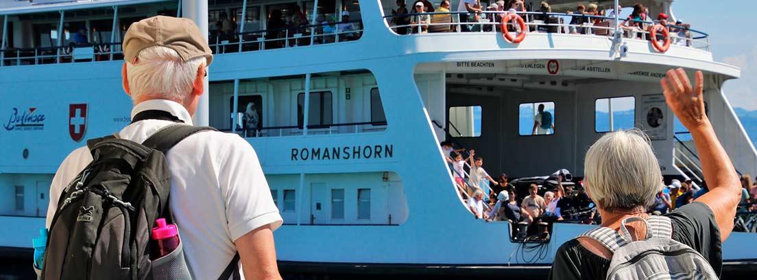 Dos personas mayores de espaldas saludando a las personas de un crucero