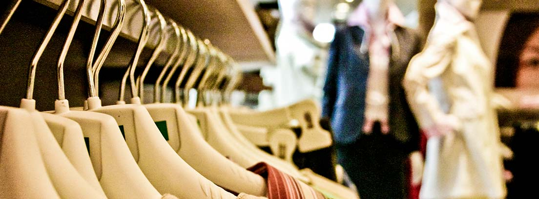 Primer plano de unas perchas con ropa y unos maniquíes dentro de una tienda