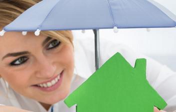 Mujer mira silueta de casa verde bajo paraguas