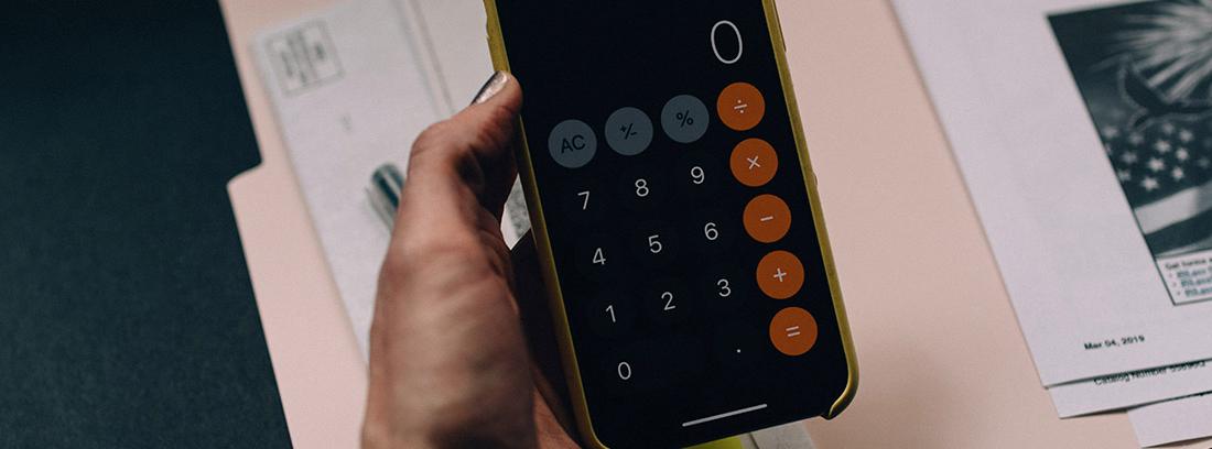 Mano sujeta una calculadora con pantalla con el número cero y sobre papeles
