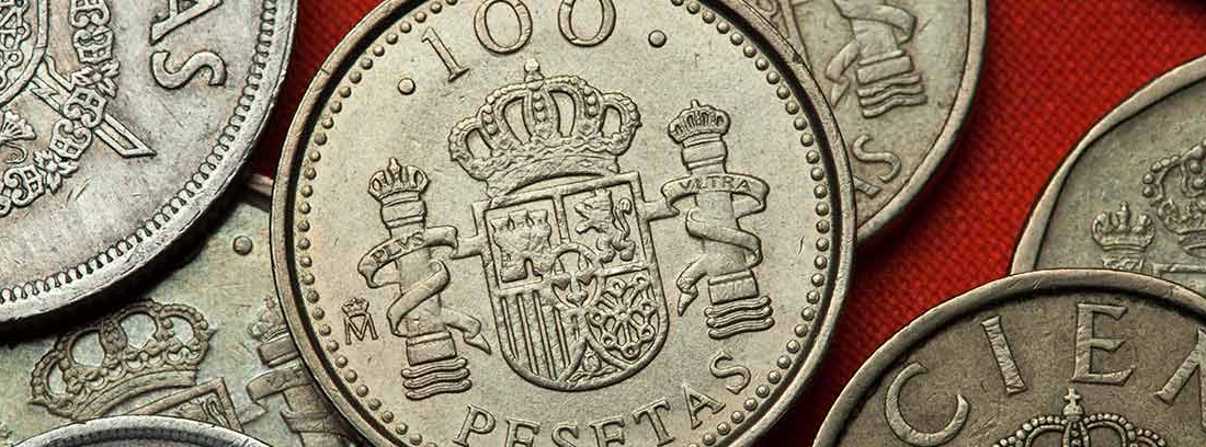 Primer plano de una moneda de 100 pesetas sobre un montón