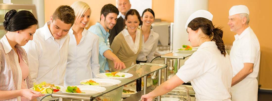 Cocineros sirviendo comida a trabajadores de una empresa