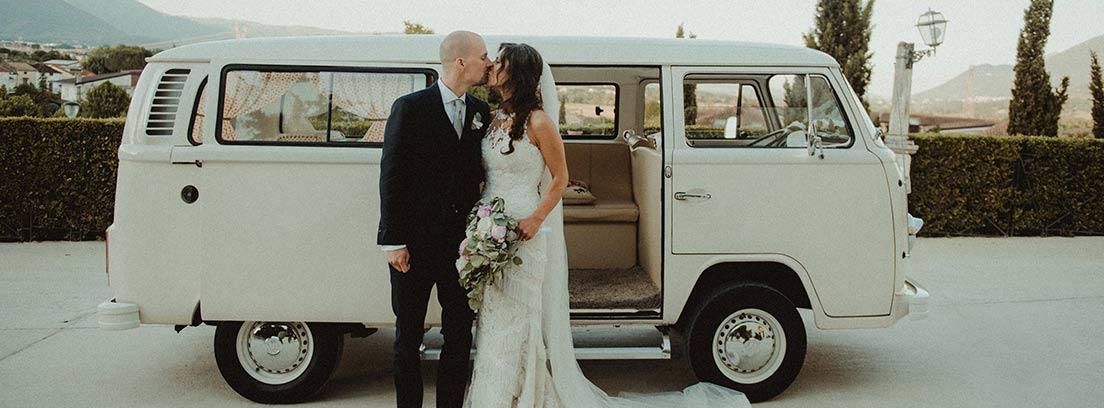 Pareja de novios besándose delante de una furgoneta blanca