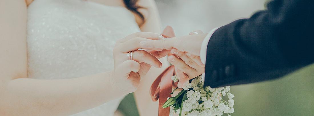 Mujer con traje de novia pone alianza en dedo de persona con traje oscuro