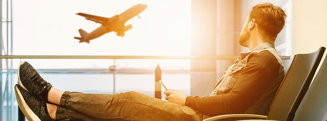 Hombre sentado con pies sobre maleta mira avión despegando