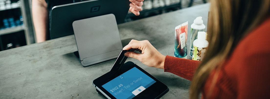 Mujer coloca tarjeta de pago en lector frente a otra mujer detrás de mostrador