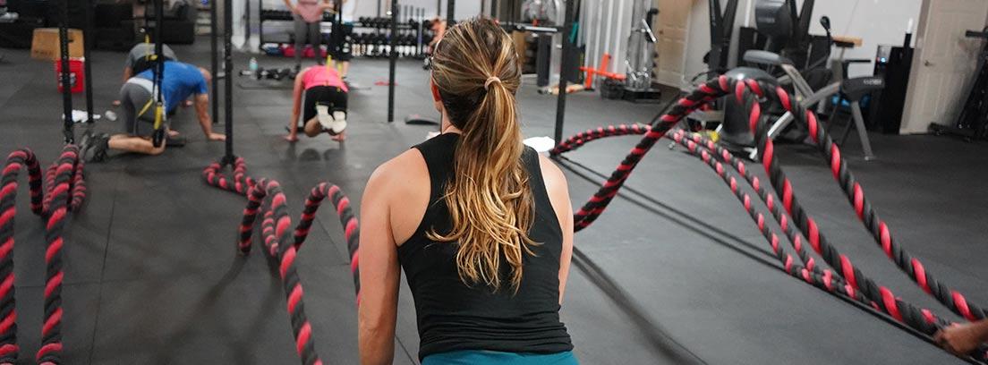 Una mujer hace crossfit en un pequeño gimnasio